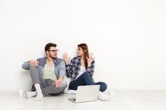 Le coppie casuali discutono qualche cosa di seduta sgradevole con il computer portatile, colpo dello studio Immagini Stock Libere da Diritti