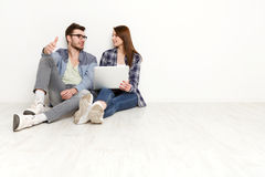 Le coppie casuali discutono qualcosa che si siede con il computer portatile, colpo dello studio Immagine Stock