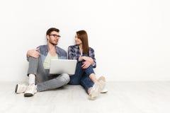 Le coppie casuali discutono qualcosa che si siede con il computer portatile, colpo dello studio Fotografia Stock Libera da Diritti