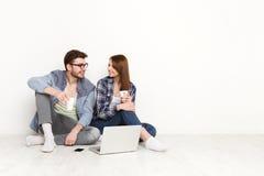 Le coppie casuali discutono qualcosa che si siede con il computer portatile, colpo dello studio Immagini Stock