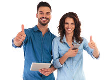 Le coppie casuali fanno il segno giusto mentre tengono i dispositivi mobili Immagine Stock