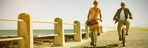Le coppie casuali felici che vanno per una bici guidano sul pilastro Immagini Stock Libere da Diritti
