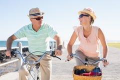 Le coppie casuali felici che vanno per una bici guidano sul pilastro Fotografia Stock Libera da Diritti