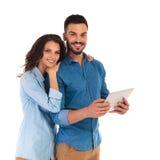 Le coppie casuali felici sorridenti con una compressa riempiono il computer Immagine Stock
