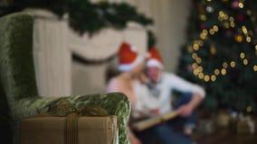 Le coppie che celebrano il Natale considerano un album delle foto adorabili stock footage