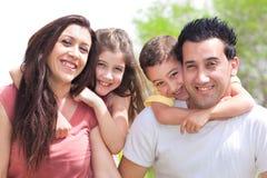 Le coppie che danno due bambini in giovane età trasportano sulle spalle fotografia stock