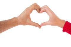 Le coppie che fanno il cuore modellano con le mani Immagini Stock