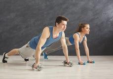 Le coppie che fanno la plancia o spingono aumentano l'esercizio all'interno Fotografie Stock