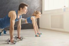 Le coppie che fanno la plancia o spingono aumentano l'esercizio all'interno Fotografia Stock Libera da Diritti