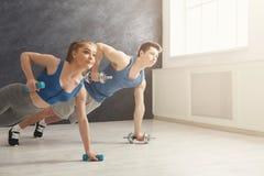 Le coppie che fanno la plancia o spingono aumentano l'esercizio all'interno Fotografia Stock