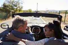 Le coppie che guidano in automobile senza coperchio se esaminano, vista posteriore Fotografia Stock