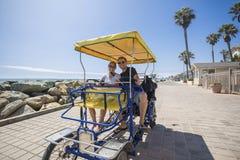 Le coppie che guidano una bici di Surrey guidano lungo la costa della California Immagine Stock