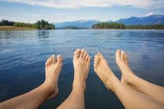 Le coppie che si rilassano su un bello lago mountain puntellano Fotografia Stock