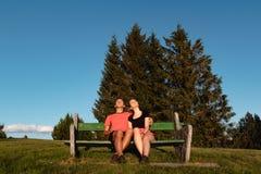 Le coppie che si siedono sul banco nelle montagne che guardano il tramonto e la presa si abbronzano fotografia stock