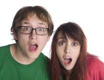 Le coppie colpite con la bocca aprono l'esame della macchina fotografica Fotografie Stock Libere da Diritti