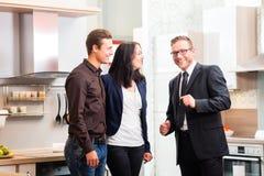 Le coppie consultano il rappresentante per la cucina domestica Fotografia Stock
