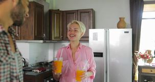 Le coppie in cucina bevono Juice In Morning arancio, il giovane e prima colazione di conversazione della donna stock footage