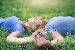 Le coppie degli amanti si rilassano sul prato Fotografie Stock