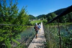 Le coppie dei turisti camminano sul ponte di legno sospeso sopra un fiume della montagna Fotografia Stock