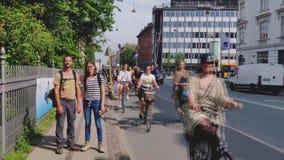 Le coppie dei turisti stanno stando sul marciapiede Ora di punta nel centro di Copenhaghen Molti ciclisti stanno guidando vicino stock footage