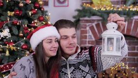 Le coppie del lovele del primo piano che esaminano il candeliere e che sorridono, godono della celebrazione di Natale stock footage