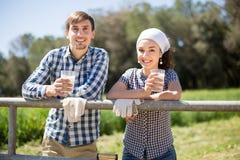 Le coppie del paese degli agricoltori bevono il latte nel campo vicino a fenc Fotografie Stock