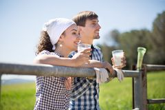 Le coppie del paese degli agricoltori bevono il latte nel campo vicino a fenc Immagini Stock Libere da Diritti