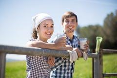 Le coppie del paese degli agricoltori bevono il latte nel campo vicino a fenc Fotografia Stock Libera da Diritti
