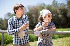 Le coppie del paese degli agricoltori bevono il latte nel campo vicino a fenc Fotografie Stock Libere da Diritti