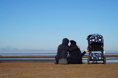 Le coppie del seme con carrozzina si siedono sulla spiaggia in primavera immagine stock