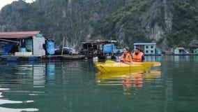 Le coppie del viaggio turistico in villaggio di galleggiamento in Halong abbaiano video d archivio