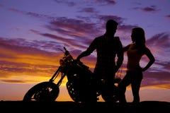 Le coppie della siluetta fanno una pausa il motociclo Fotografie Stock