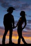 Le coppie della siluetta si tengono per mano il cowboy Immagini Stock