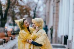 Le coppie di amore, il tipo e la sua amica vestiti in impermeabili gialli stanno abbracciando sulla via nella pioggia fotografia stock libera da diritti