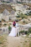 Le coppie di amore di San Valentino negli abbracci e baci della natura, uomo e donna si amano Montagne del cappadocia in tacchino fotografia stock libera da diritti