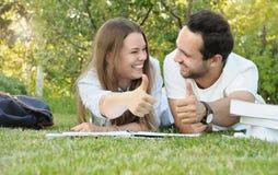 Le coppie di giovani studenti si divertono mentre studing nel parco Immagine Stock Libera da Diritti