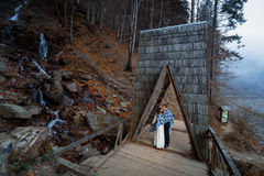Le coppie di nozze baciano morbidamente sul ponte di legno Giorno nebbioso in montagne Immagini Stock Libere da Diritti
