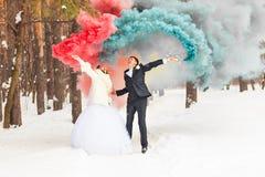 Le coppie di nozze con colore fumano nel parco dell'inverno immagine stock
