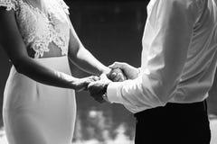 Le coppie di nozze stanno sul pilastro di legno e tengono le mani Esaminano la bella vista sopra il lago Giorno di estate soleggi fotografia stock