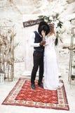 Le coppie di nozze, uomo africano e donna caucasica, vestiti nello stile di boho stanno restando prima dell'arco di nozze, bacian immagini stock