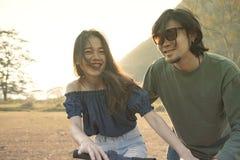 Le coppie di più giovani uomo e donna asiatici praticano a bicycl di guida Immagine Stock Libera da Diritti
