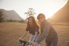 Le coppie di più giovani uomo e donna asiatici praticano a bicycl di guida Fotografie Stock