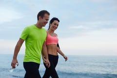 Le coppie di risata camminano lungo la spiaggia dopo addestramento di forma fisica Fotografia Stock Libera da Diritti