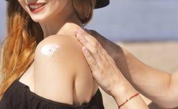 Le coppie di Suncare su una vacanza della spiaggia dell'estate hanno buon skincare con l'alto sunblock di spf Coppie che applican Fotografia Stock