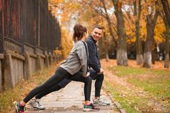 Le coppie di Theathletic sono impegnate nell'allungamento dei muscoli delle gambe del parco all'aperto Immagine Stock