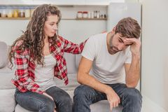 Le coppie discutono La moglie ha gridato al suo marito disperato, sedentesi sullo strato nel salone a casa Un uomo non fa immagine stock libera da diritti