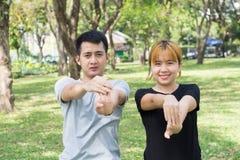 Le coppie dolci asiatiche si scaldano i loro corpi allungando le armi prima dell'esercizio pareggiante di mattina nel parco Immagine Stock