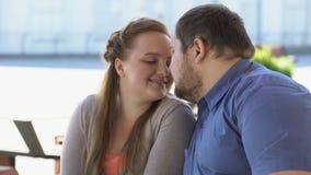 Le coppie dolci nell'amore che fruga la seduta sul banco della città, weekend insieme, la prossimità video d archivio
