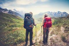 Le coppie equipaggiano e l'alpinismo di viaggiatori con zaino e sacco a pelo dei viaggiatori della donna Fotografia Stock Libera da Diritti