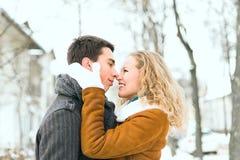 Le coppie felici all'aperto nell'amore che posa nell'inverno freddo sopravvivono Immagini Stock